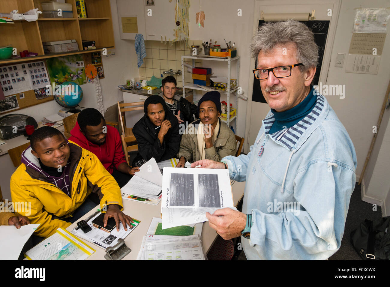 A retired social worker, working as a volunteer now (right), gives a lesson in German language to mostly African - Stock Image