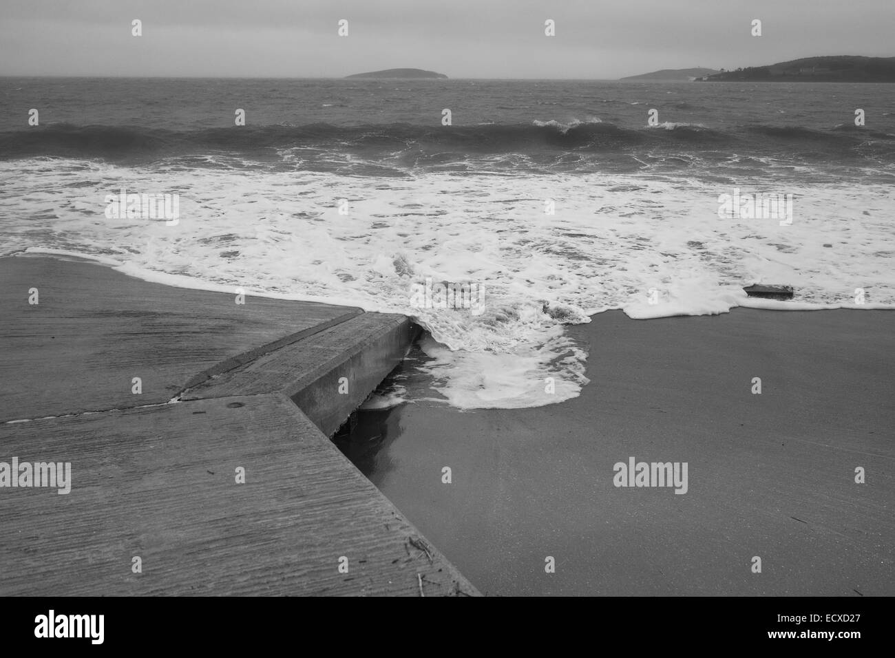 The sea breaks over a slip way in winter on Abersoch Beach, North Wales - Stock Image