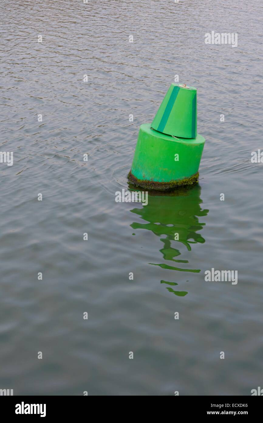 A green channel marker tilted by the tidal stream - Stock Image
