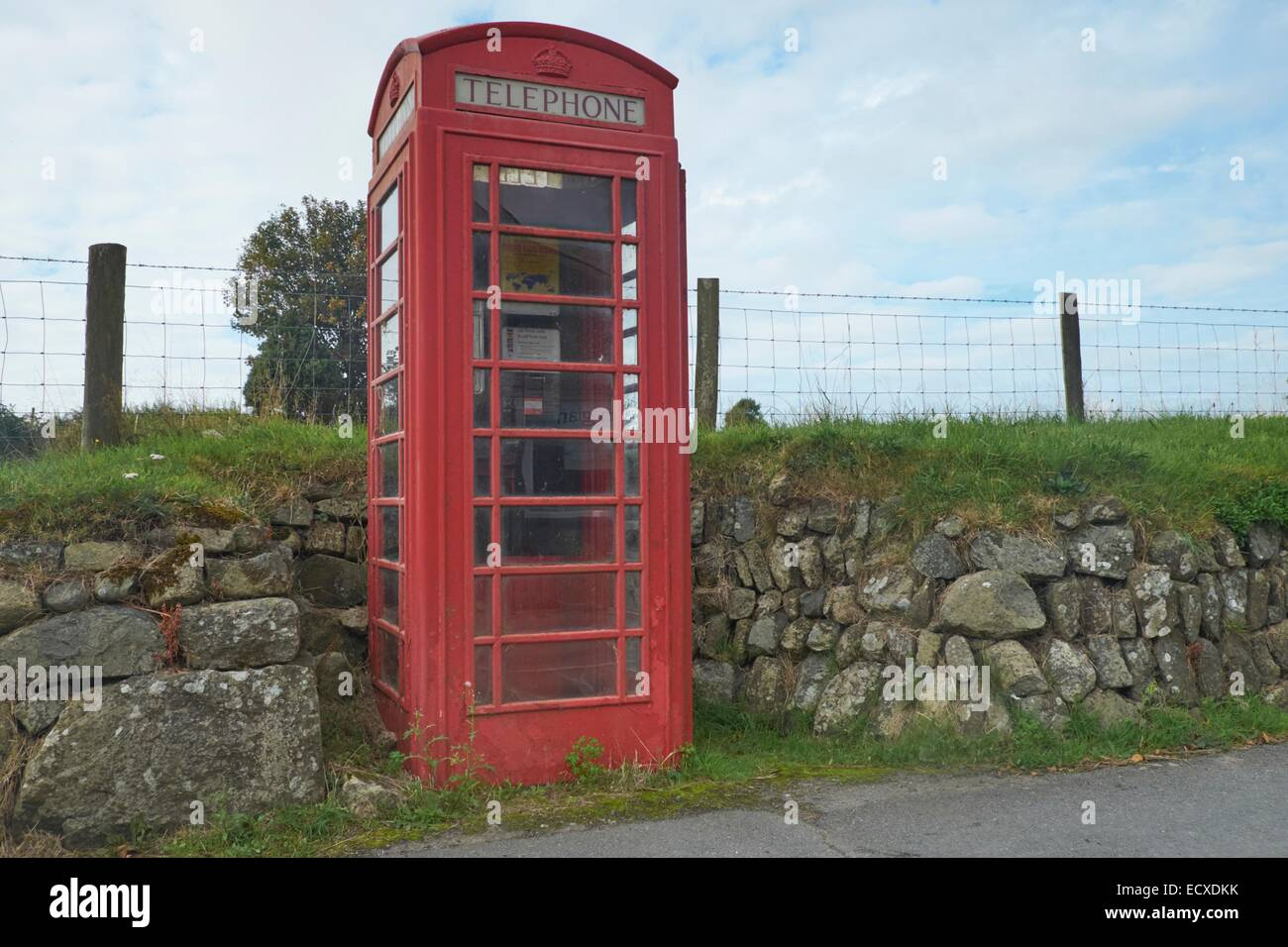 A functioning rural public telephone kiosk recessed into a dry stone wall in a Welsh village in the mobile phone - Stock Image