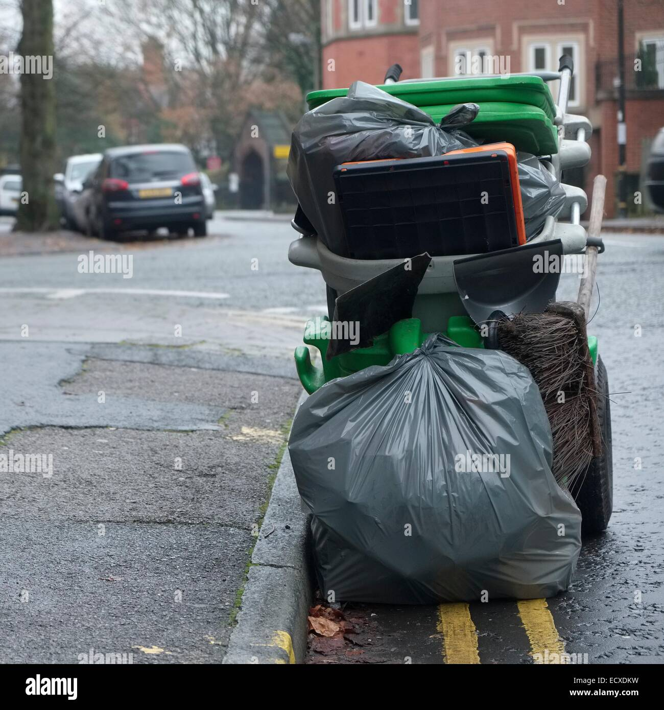 A road sweeper's trolley with black sacks of rubbish collected on his rounds in Altrincham, Cheshire - Stock Image