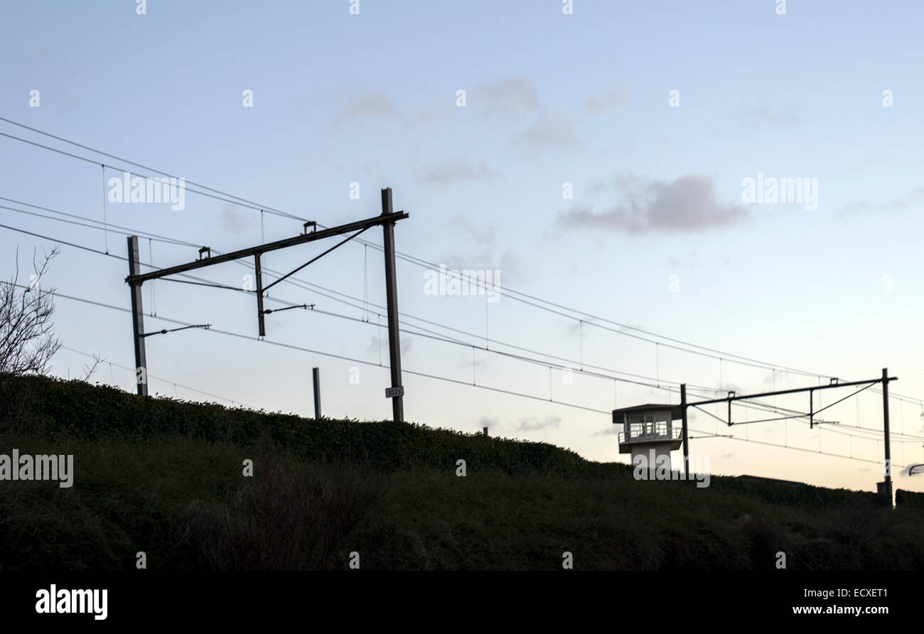 Elevated rail track with overhead power and watch tower in evening sky - Stock Image