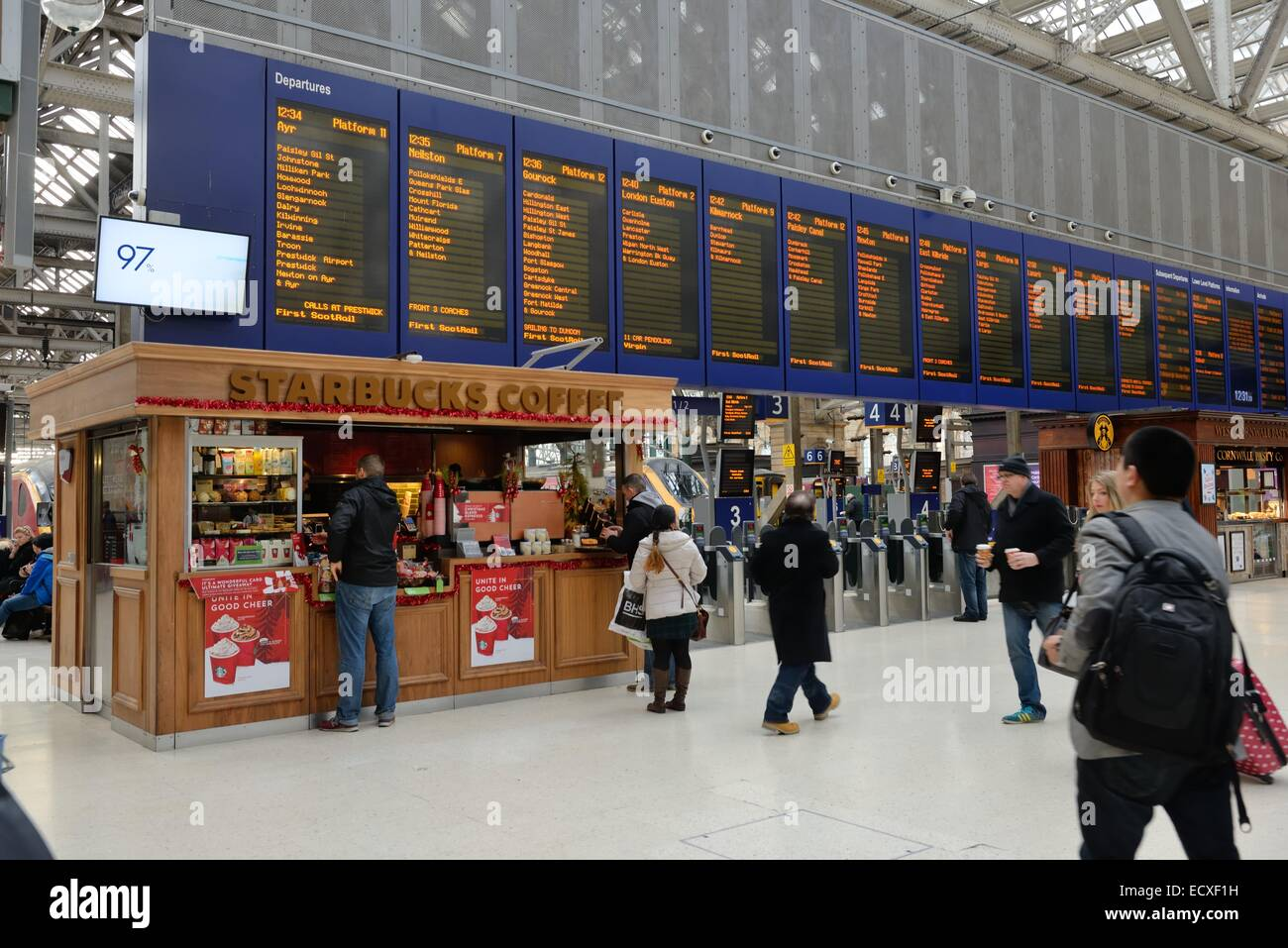A Starbucks kiosk sells coffee to rail commuters at Glasgow Central station - Stock Image