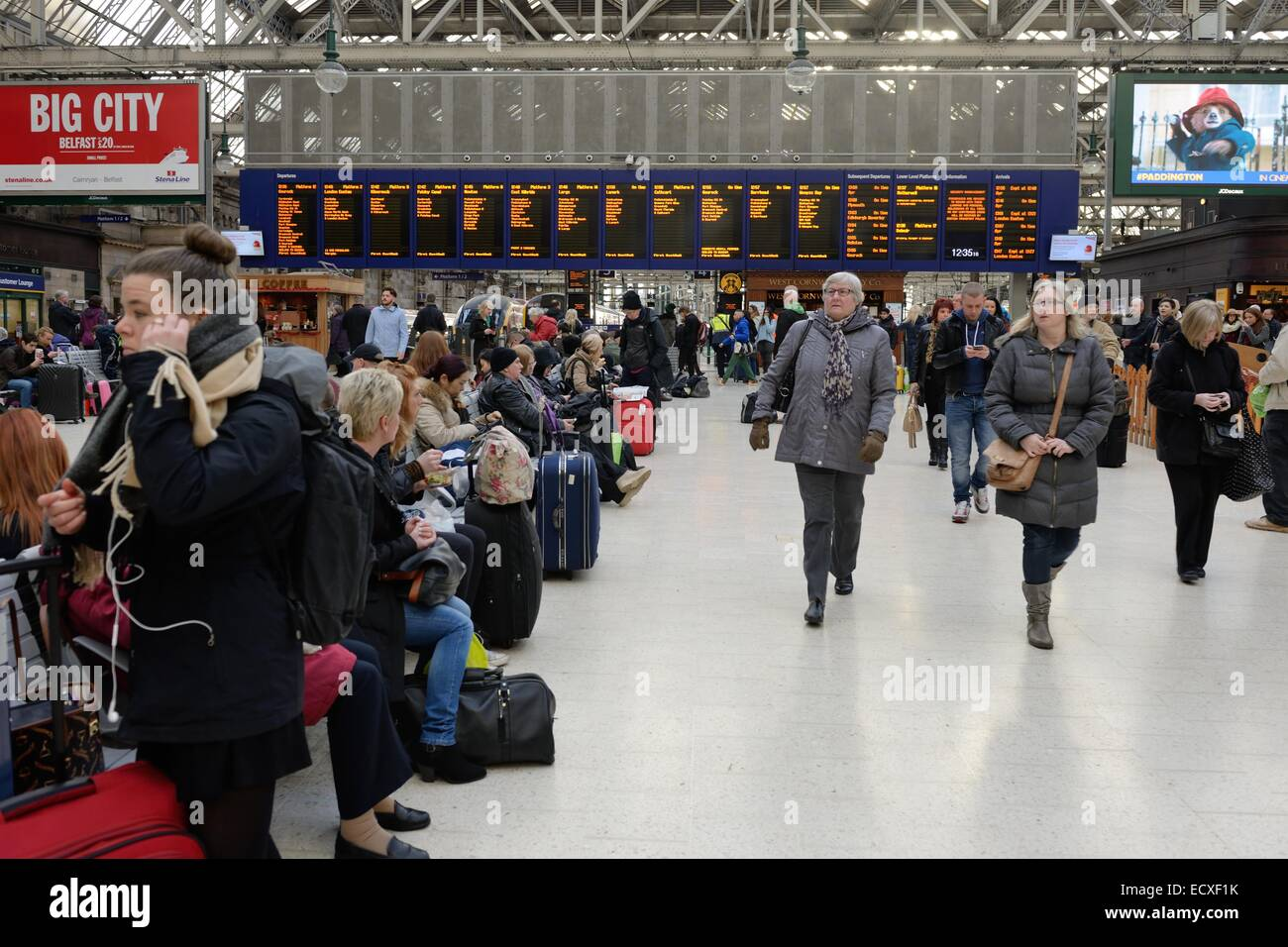 People waiting on trains at Glasgow's Central Station. - Stock Image