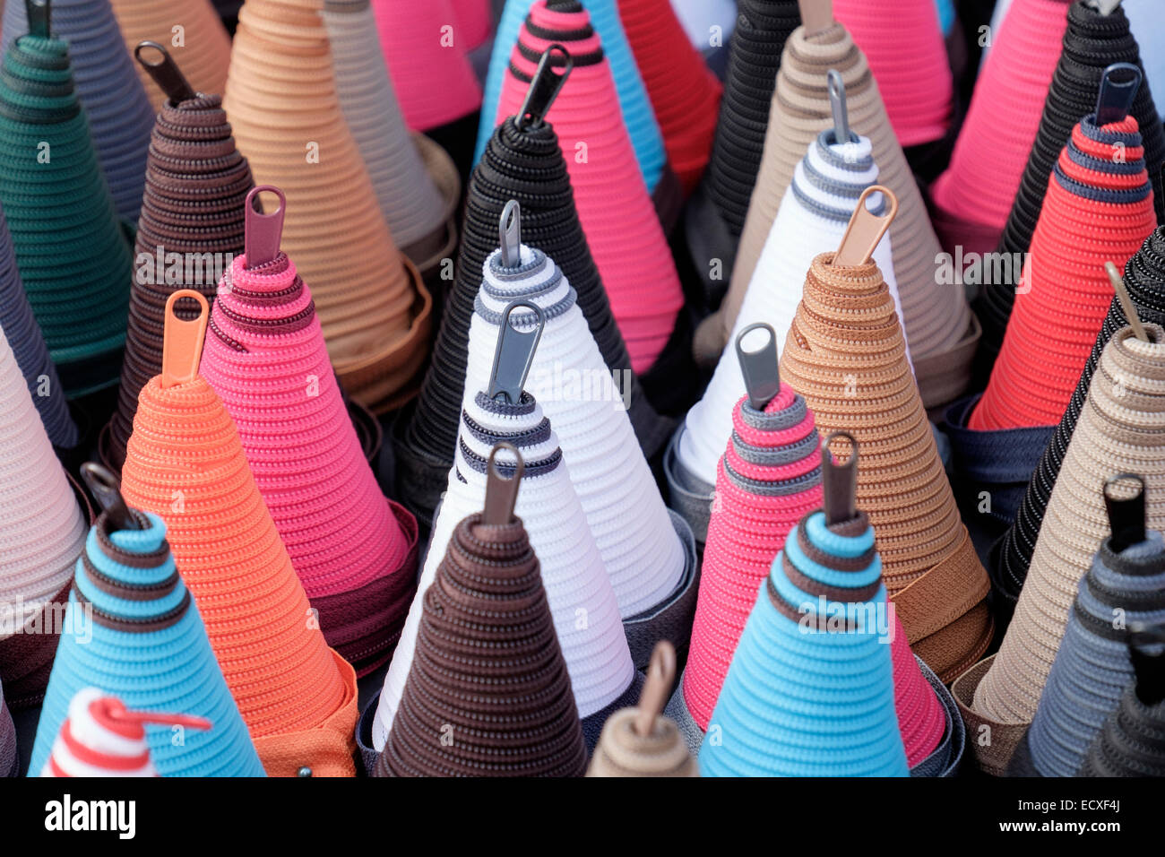 Lots of colourful zippers coiled into cone shaped spirals for sale on a market stall. France, Europe - Stock Image