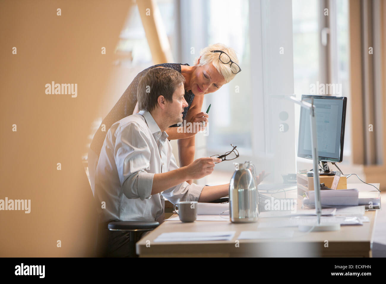 Business people talking at office desk - Stock Image