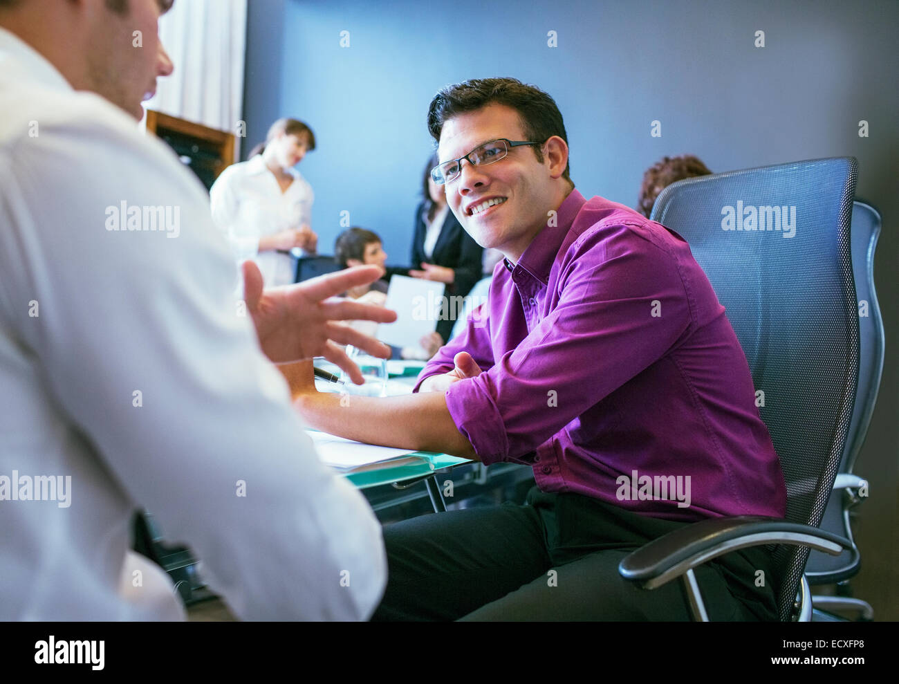 Businessmen talking during meeting in conference room with colleagues in background - Stock Image