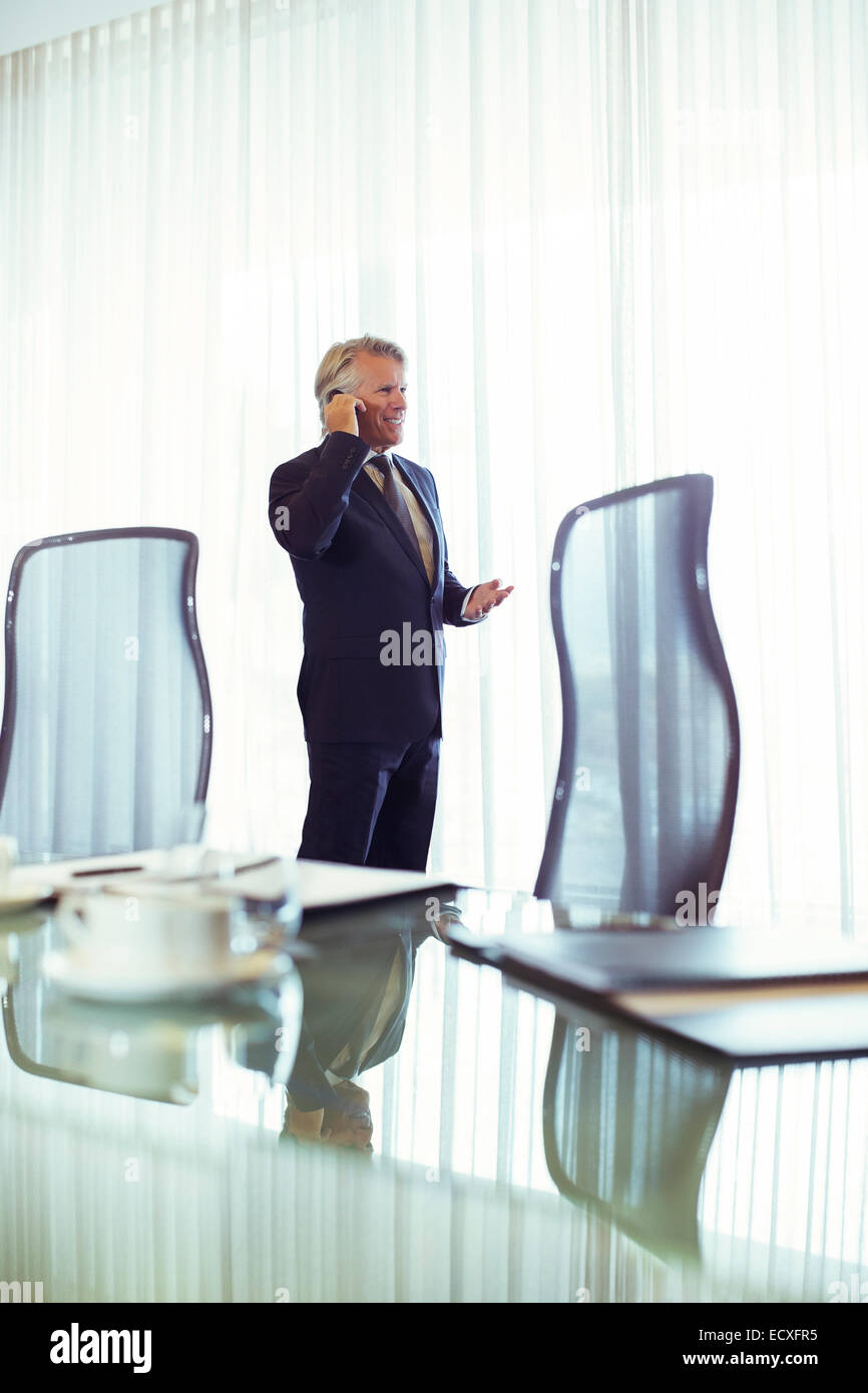 Man standing in conference room talking on his mobile phone - Stock Image