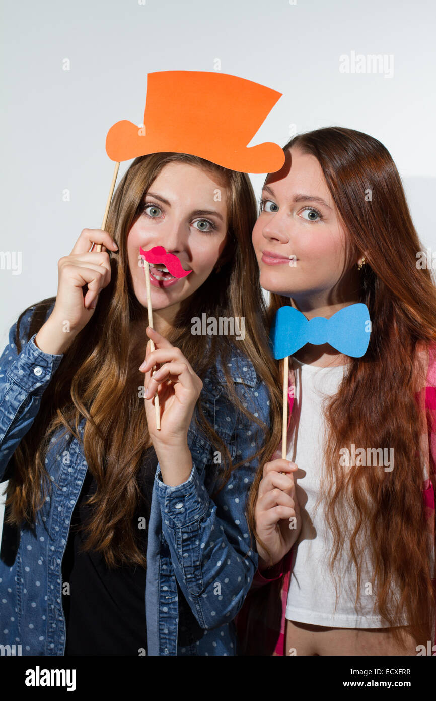 Two young women enjoying with silly props posing for pictures photo booth style - Stock Image