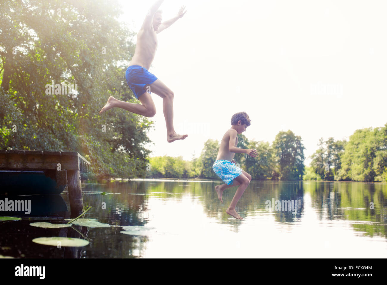 Father and son jumping into lake - Stock Image