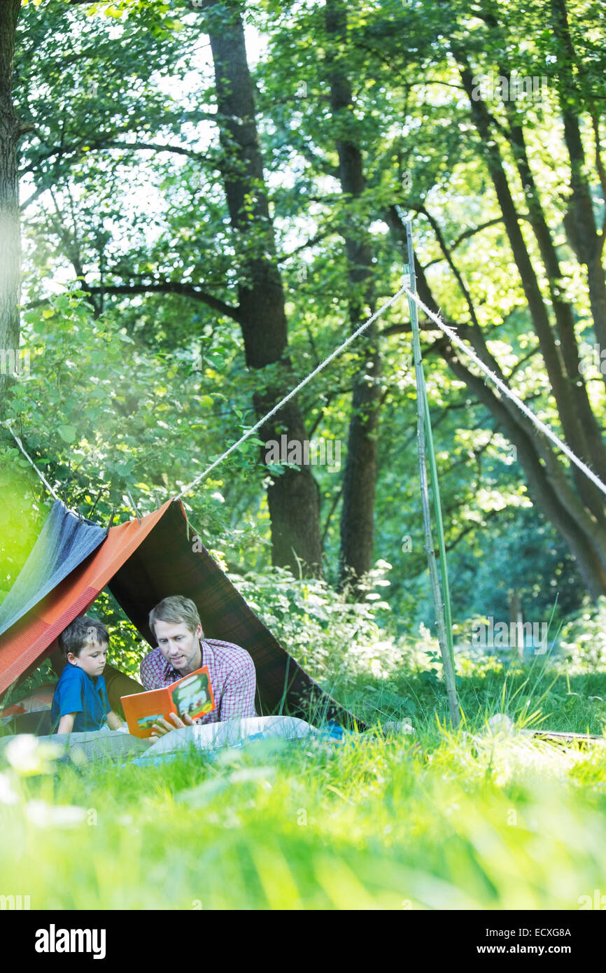 Father and son reading in camping tent - Stock Image