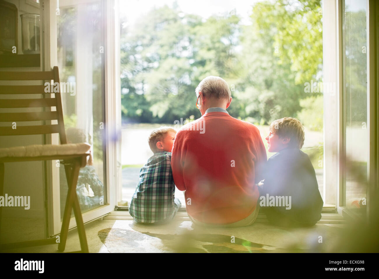 Grandfather and grandsons sitting in doorway - Stock Image