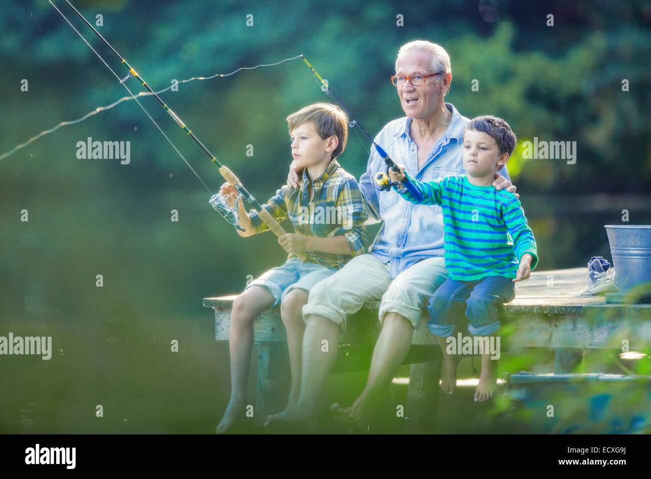 Grandfather and grandsons fishing in lake - Stock Image