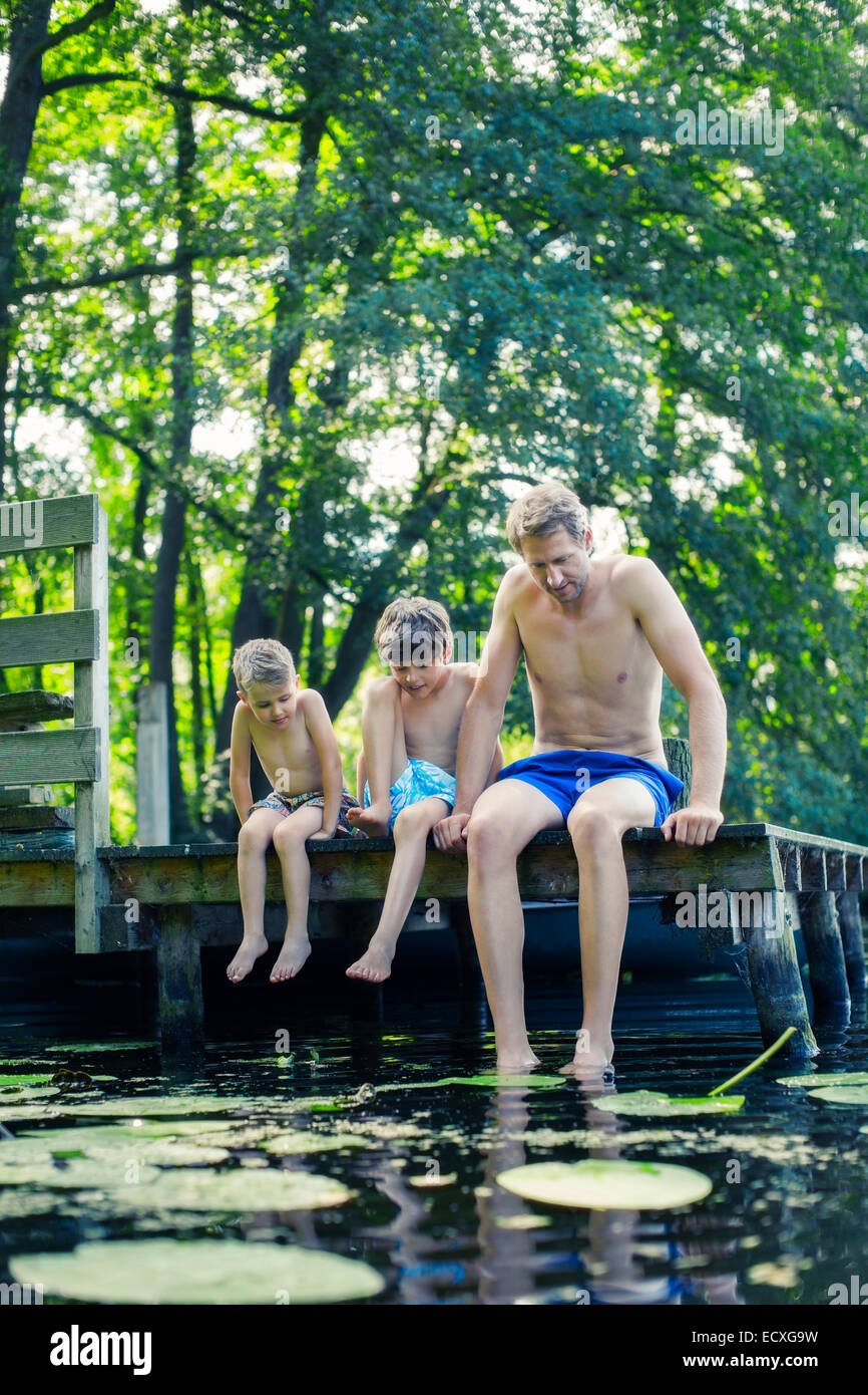 Father and sons dangling feet in lake - Stock Image