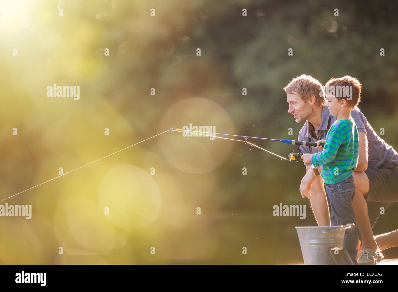 Father and son fishing in lake - Stock Image