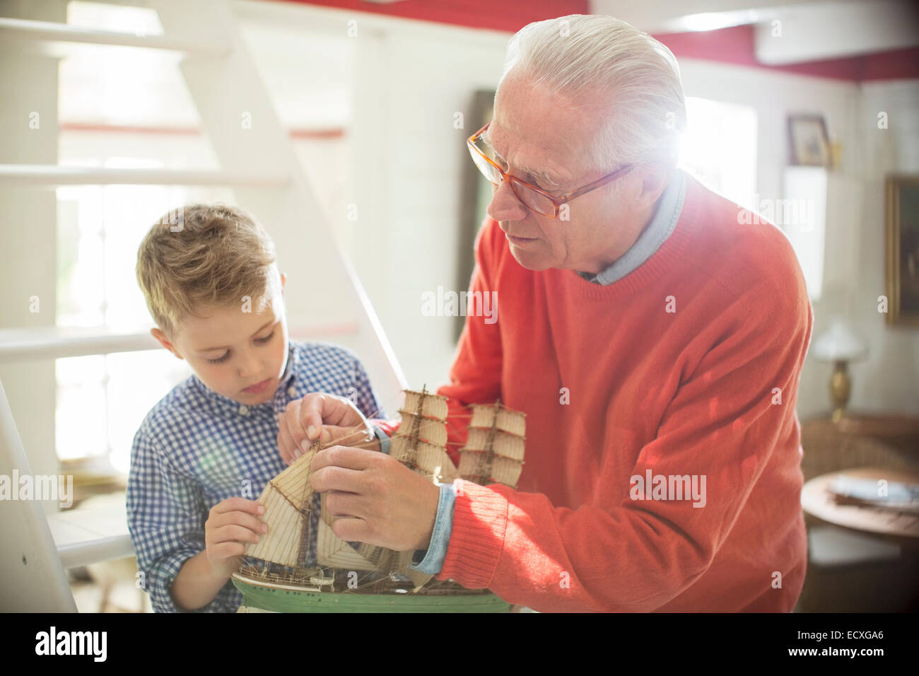 Grandfather and grandson building model sailboat - Stock Image