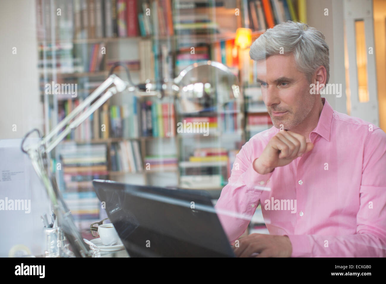 Businessman working on laptop in home office - Stock Image