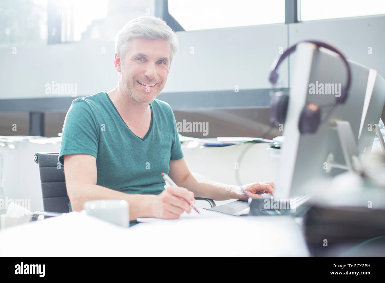 Older man working on computer at desk - Stock Image