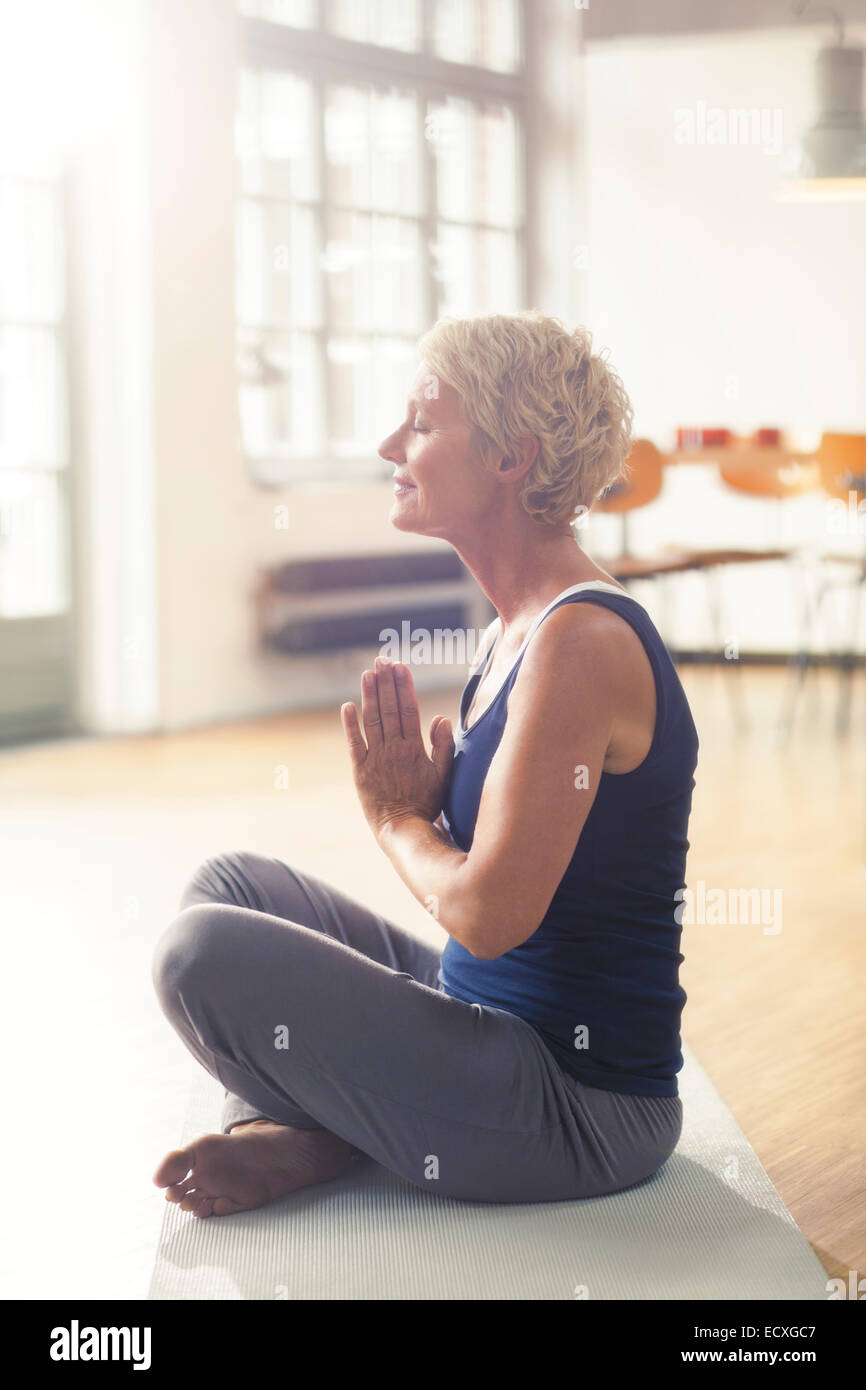 Older woman meditating on exercise mat - Stock Image