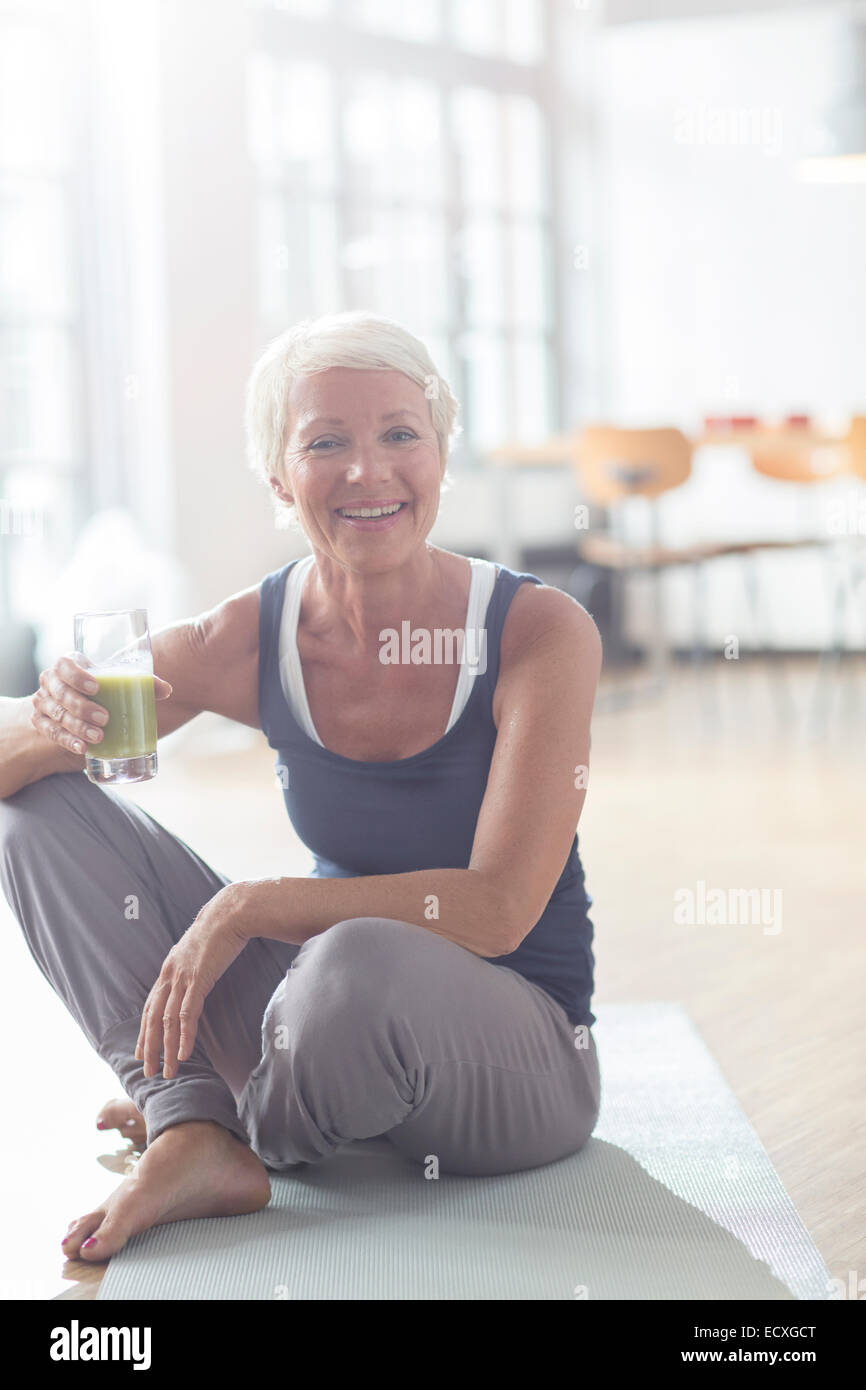 Older woman drinking juice on exercise mat - Stock Image
