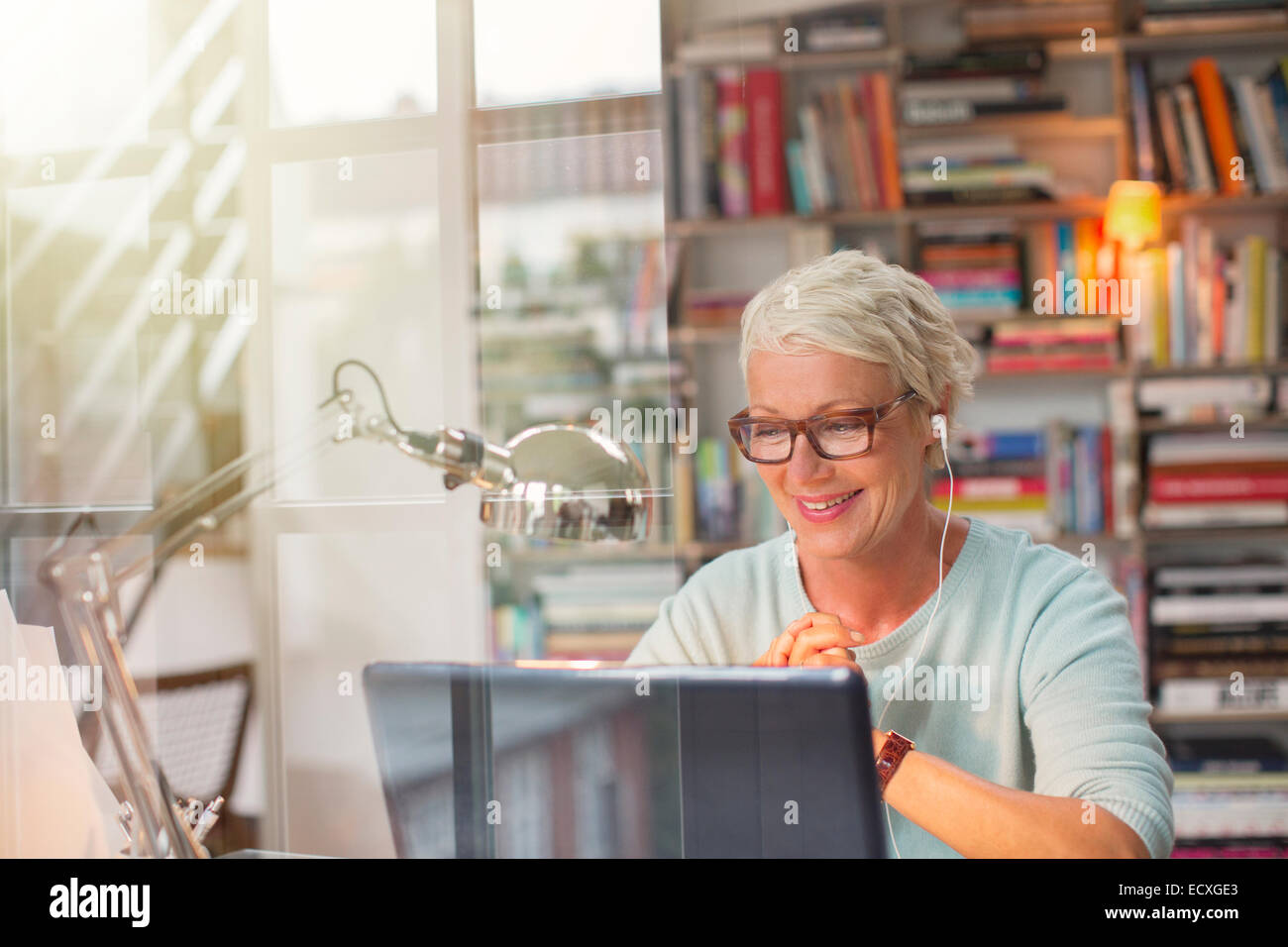 Businesswoman listening to earbuds and working in home office Stock Photo
