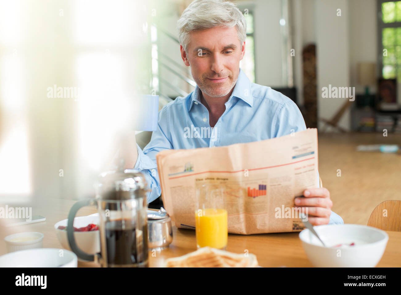 Older man reading newspaper at breakfast table Stock Photo