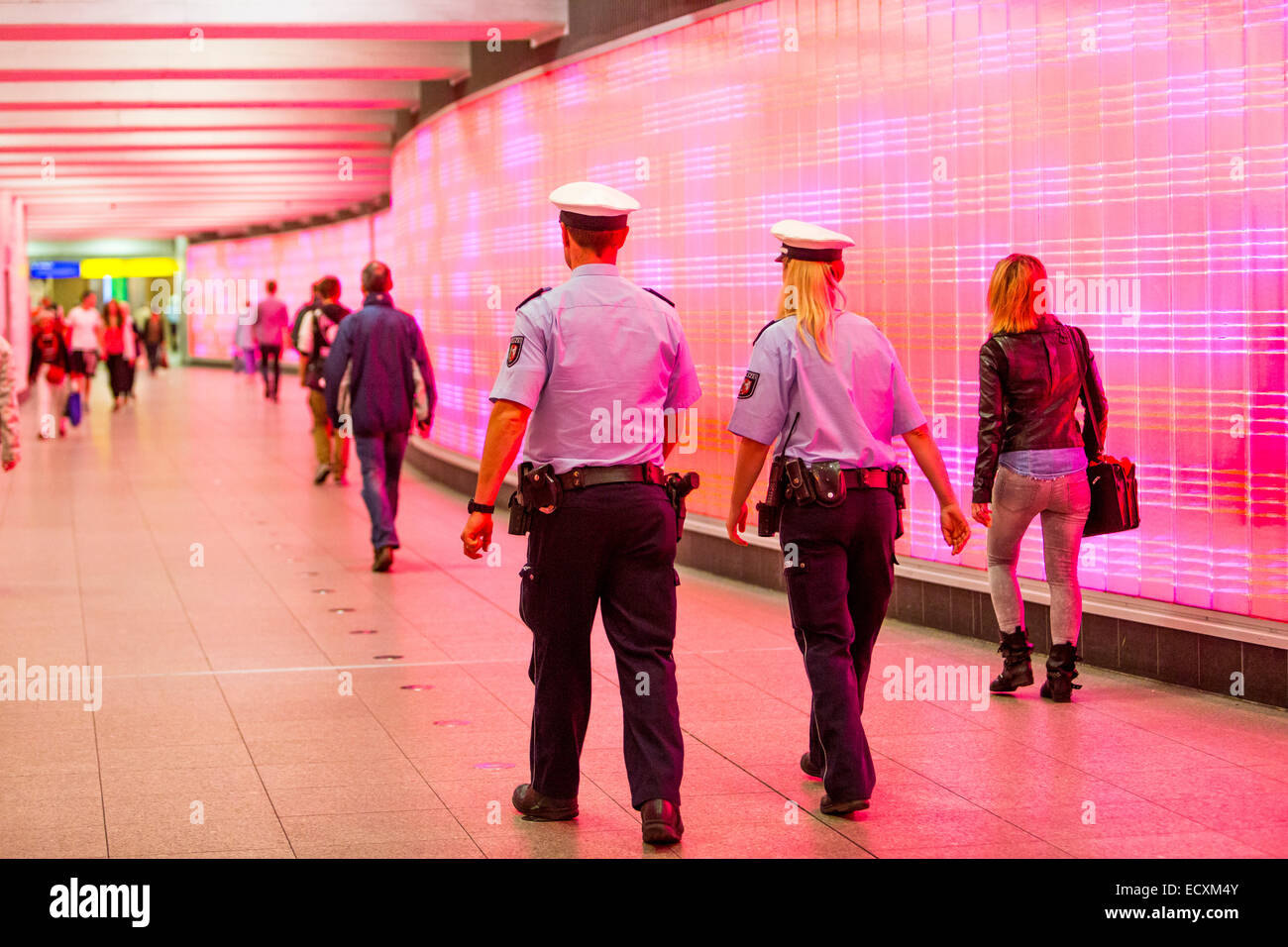 Passengers in an underground passage with a wall of lights, police patrol, - Stock Image