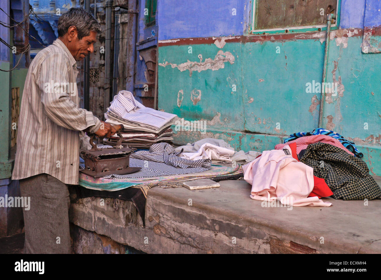 Man ironing clothing outside his home in the Blue City, Jodhpur, Rajasthan, India - Stock Image