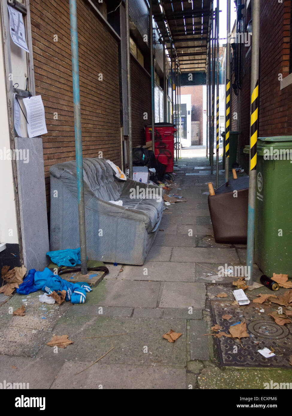 Fly tip in a side alley, containing Sofa's and refuse bags - Stock Image