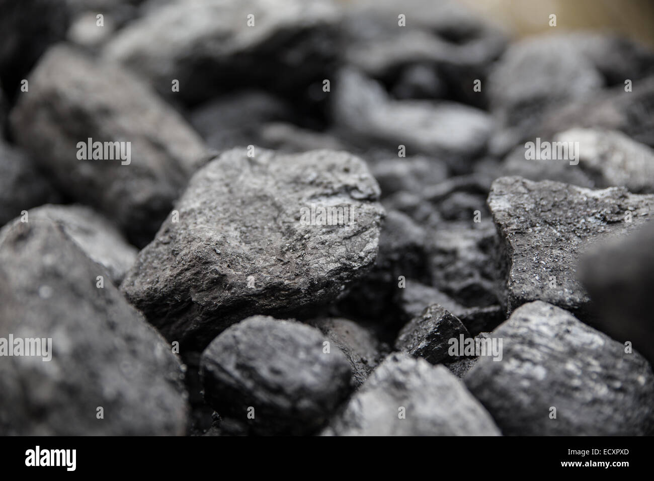 Shallow depth of field photo of lumps of coal piled up. - Stock Image