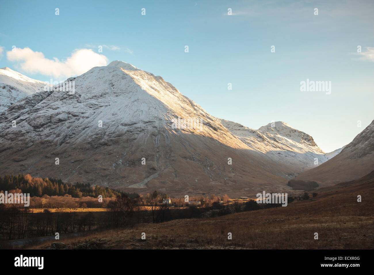 Afternoon sun on the snowy volcanic peaks of Glen Coe, Scotland, in the Scottish Highlands. A farmhouse is lit by - Stock Image
