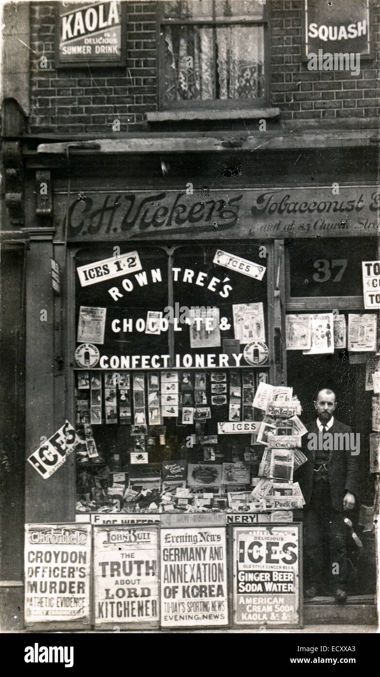 Old Postcard, 1910. Man standing in doorway of newsagent, newspaper shop, Croydon, London. Black and white photograph - Stock Image
