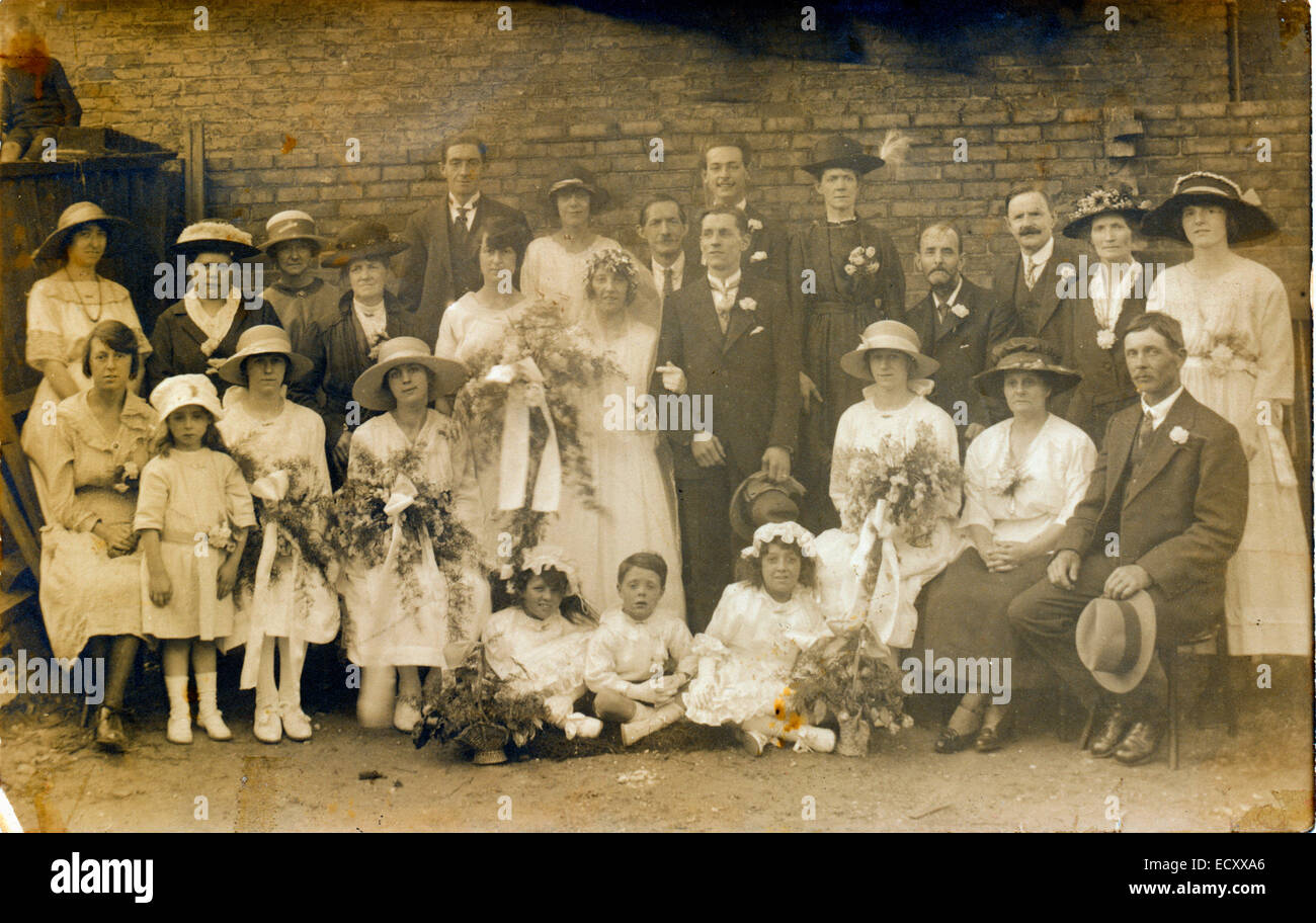 1920's Sepia group photograph of wedding, extended families posing gathered around bride and bridegroom. - Stock Image