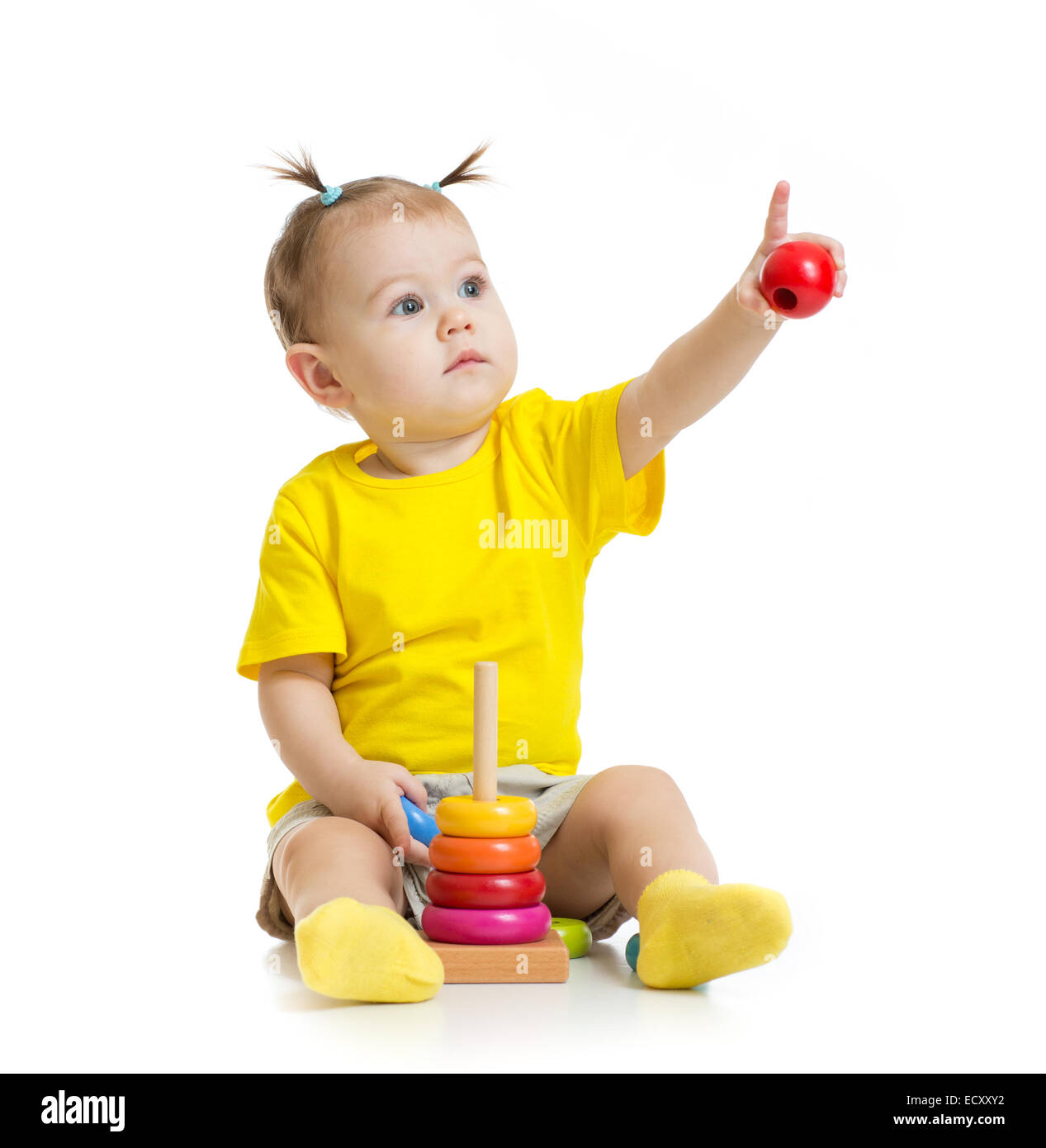 baby playing with colorful toy and pointing by finger isolated - Stock Image