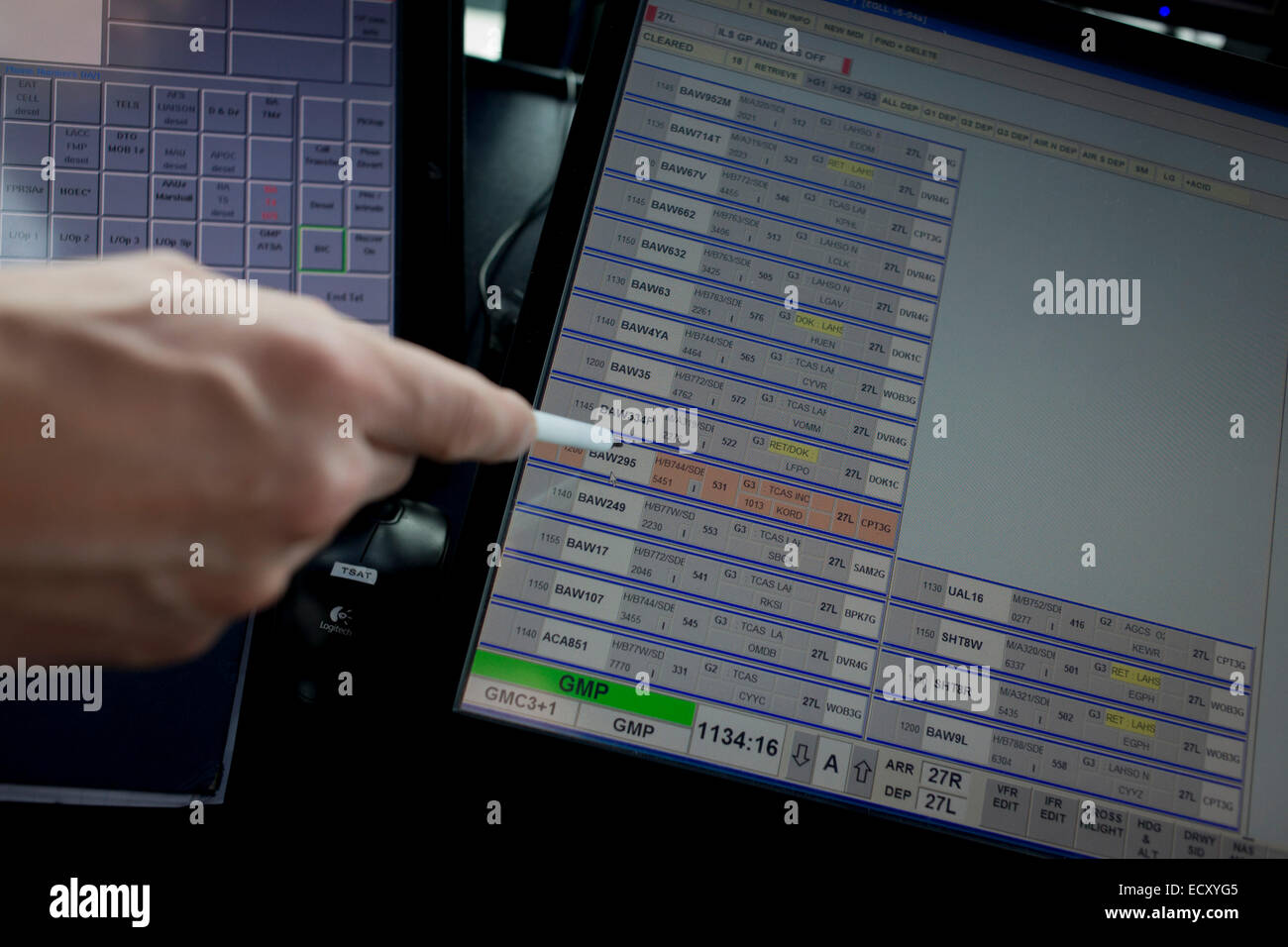 Detail of NATS air traffic controller's hand pointing to flight IDs on screen in control tower at Heathrow airport, - Stock Image