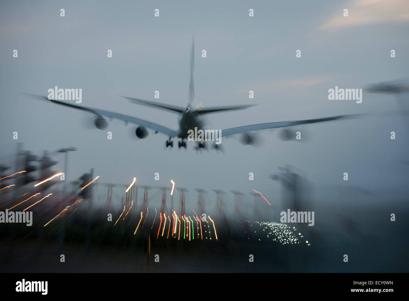 With bright landing lights on, blurred jet airliner lands at London Heathrow airport. - Stock Image