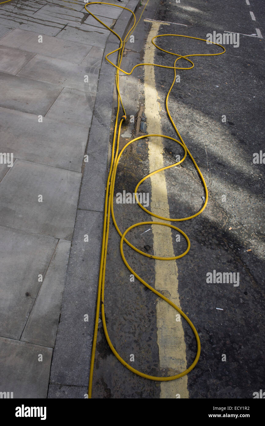 Coils and loops of yellow hosepipe on the ground in a south London street. - Stock Image