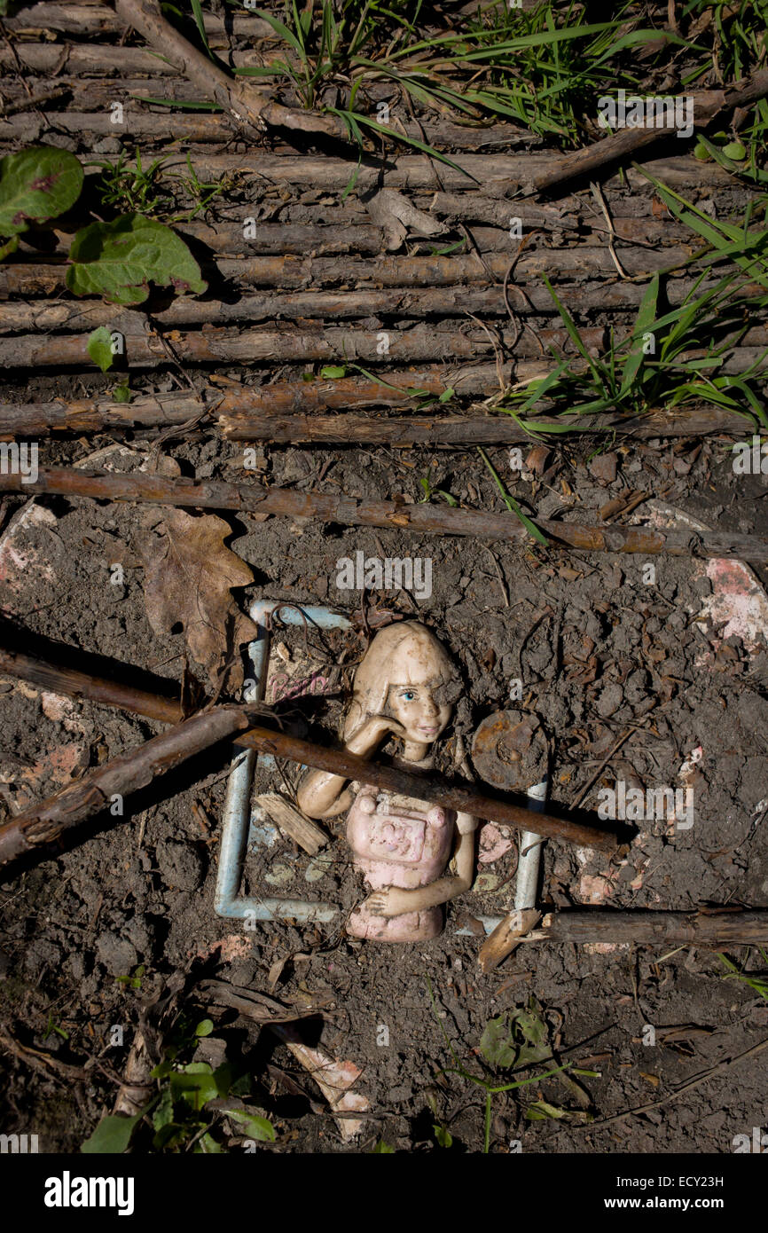 Doll trodden into soil in risk averse playground called The Land on Plas Madoc Estate, Ruabon, Wrexham, Wales. - Stock Image