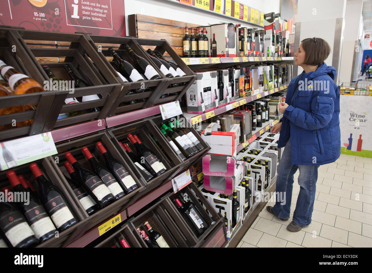 Shopper buying wine in Lidl supermarket, Mitcham, South London, UK - Stock Image