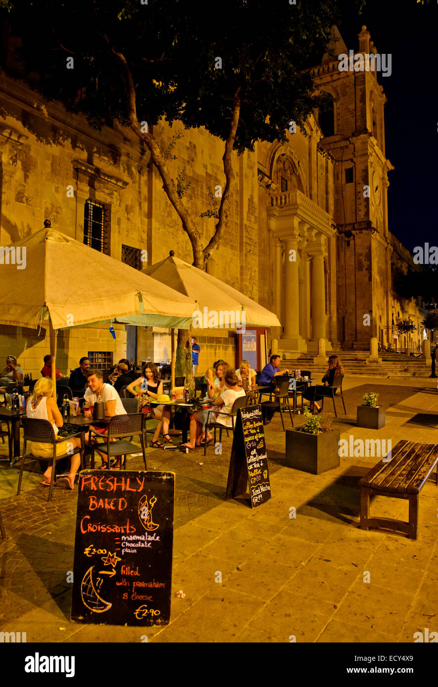 Tourists sitting in an outdoor restaurant at St. John's Co-Cathedral, European Capital of Culture 2018, Valletta, - Stock Image