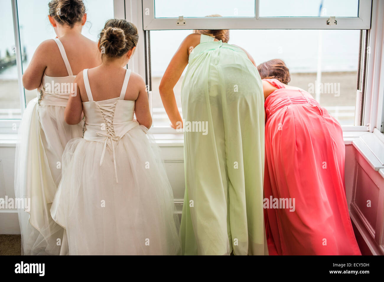 Wedding day UK: rear view of four young girls,  bridesmaids , looking out of a hotel window on the morning of the - Stock Image