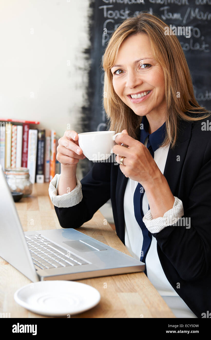 Businesswoman Using Laptop In Cafe Stock Photo