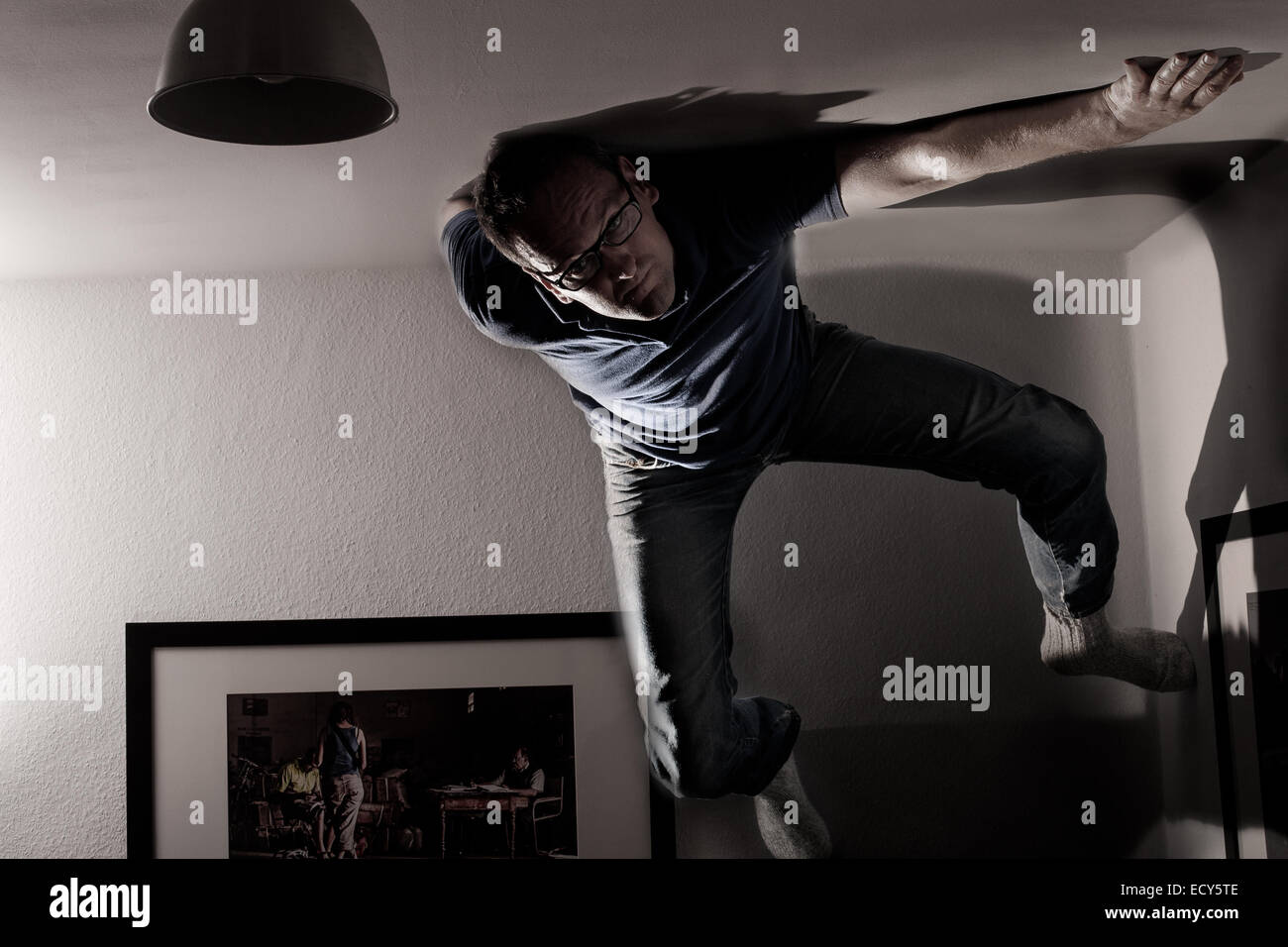 Man climbing along the ceiling. - Stock Image