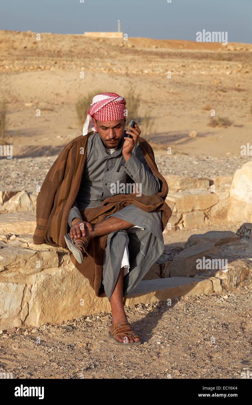 Jordanian in traditional dress on a mobile phone, desert castle Qasr Amra or Qusaie Amra, Jordan - Stock Image