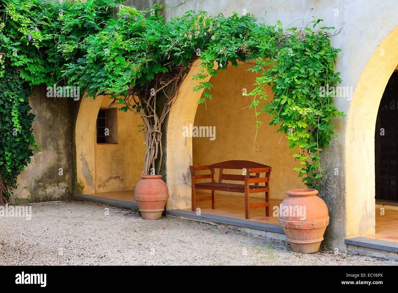Wooden bench under an arcade, Orosei, Province of Nuoro, Sardinia, Italy Stock Photo
