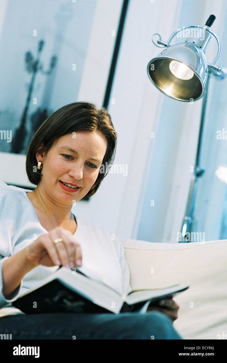 Middle-aged woman enjoys reading a book Stock Photo