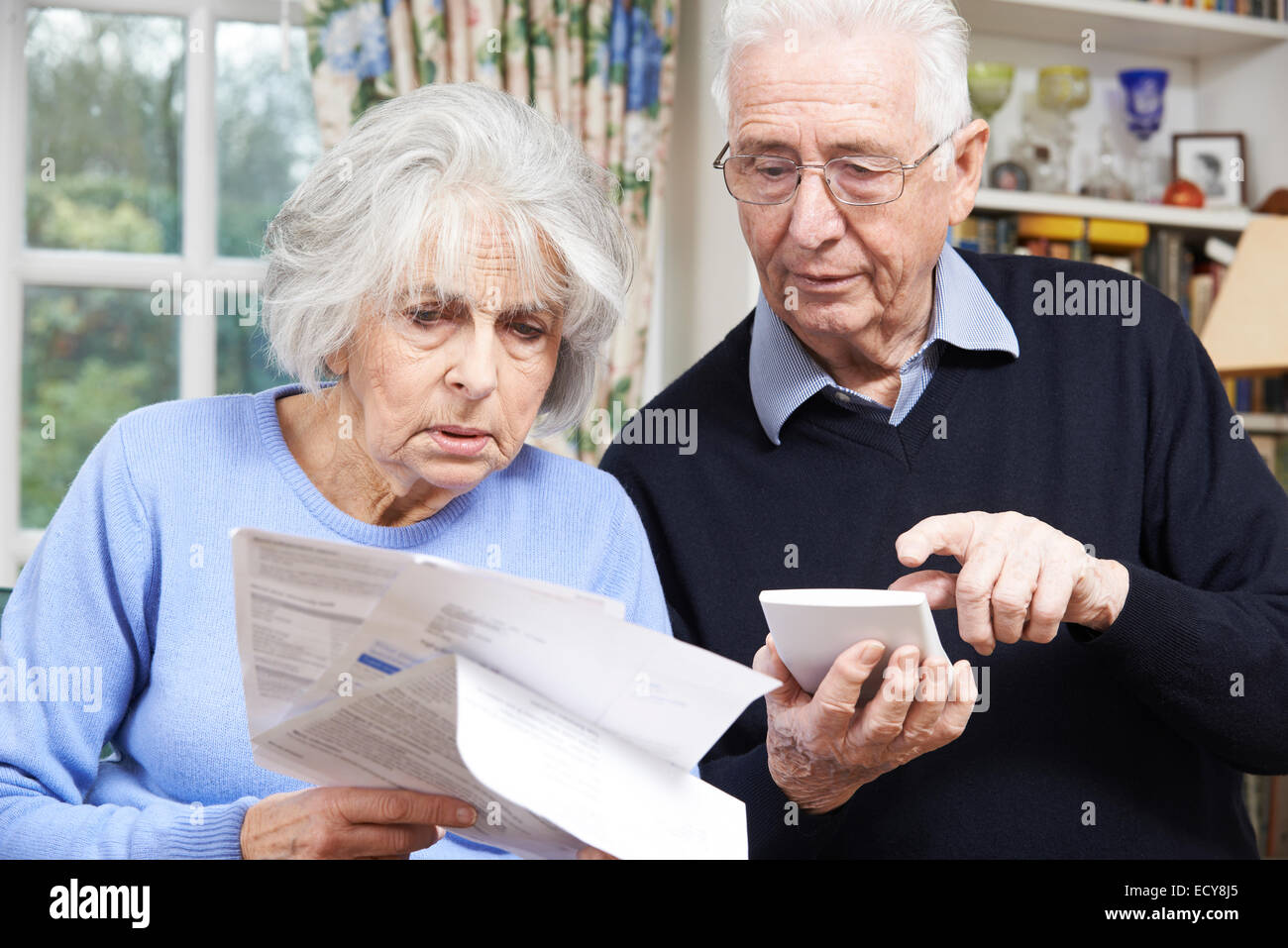 Senior Couple At Home With Bills Worried About Home Finances - Stock Image