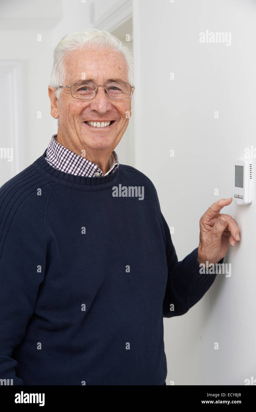 Smiling Senior Man Adjusting Central Heating Thermostat - Stock Image