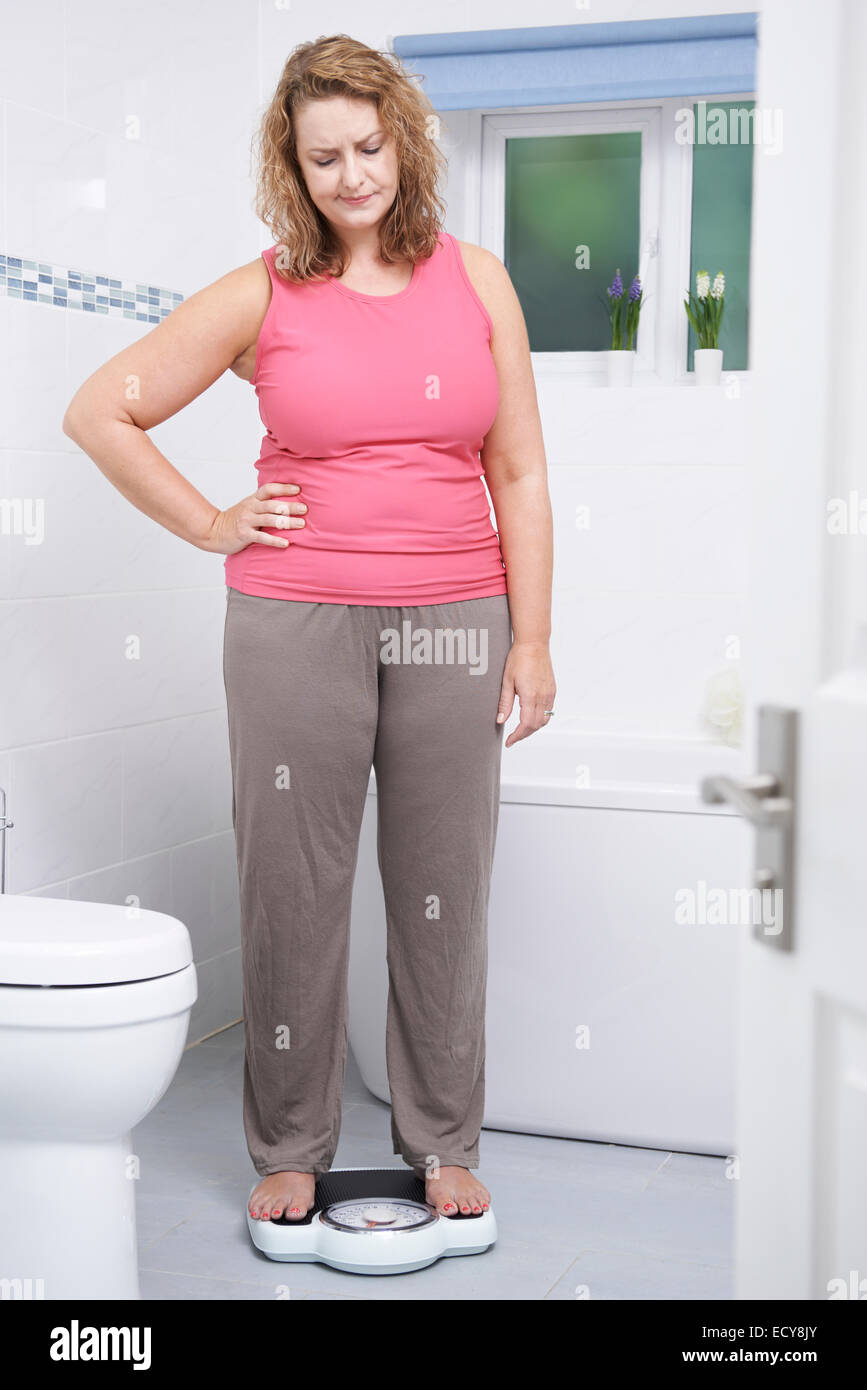 Overweight Woman Weighing Herself On Scales In Bathroom - Stock Image