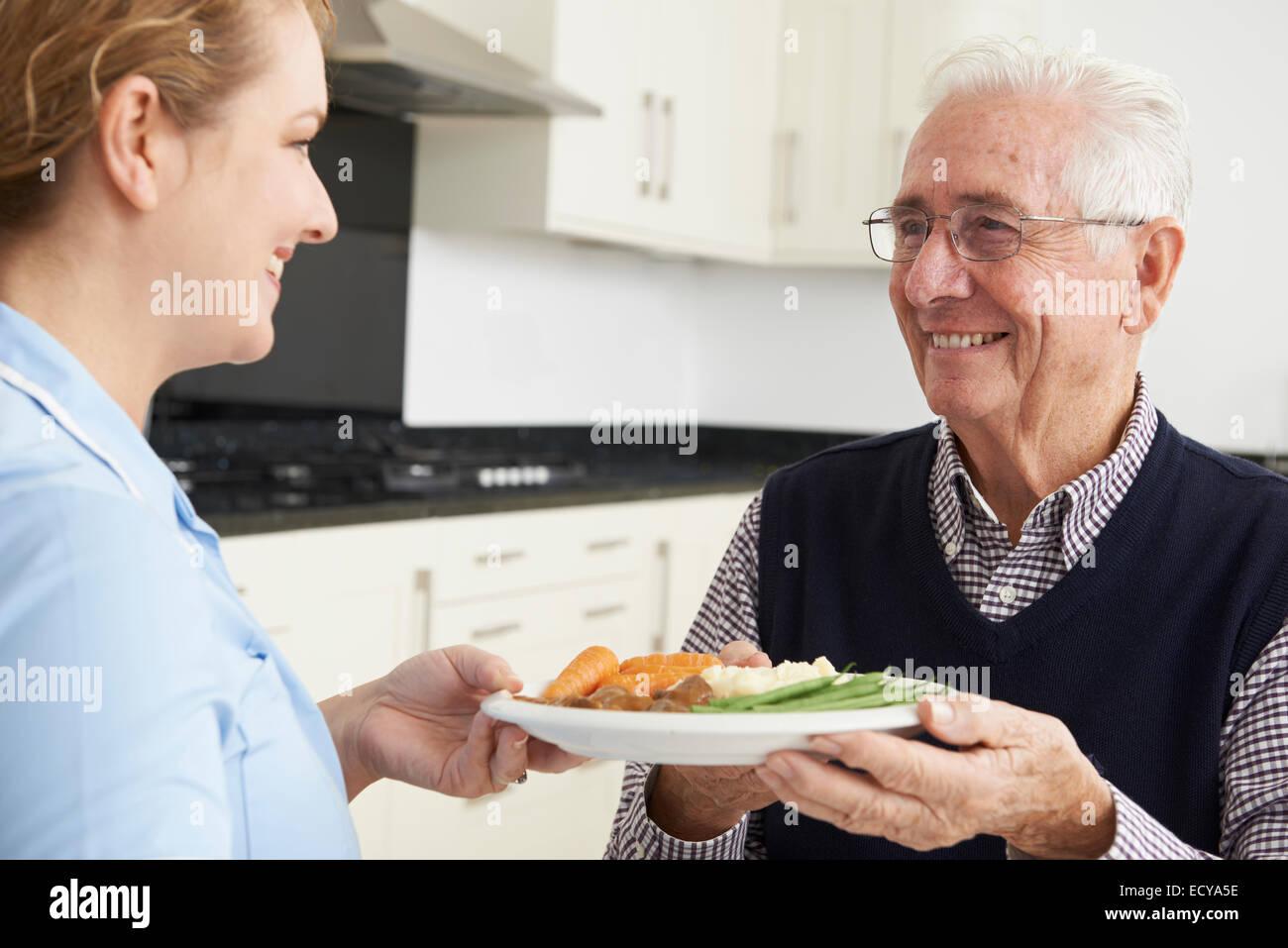 Carer Serving Lunch To Senior Man - Stock Image